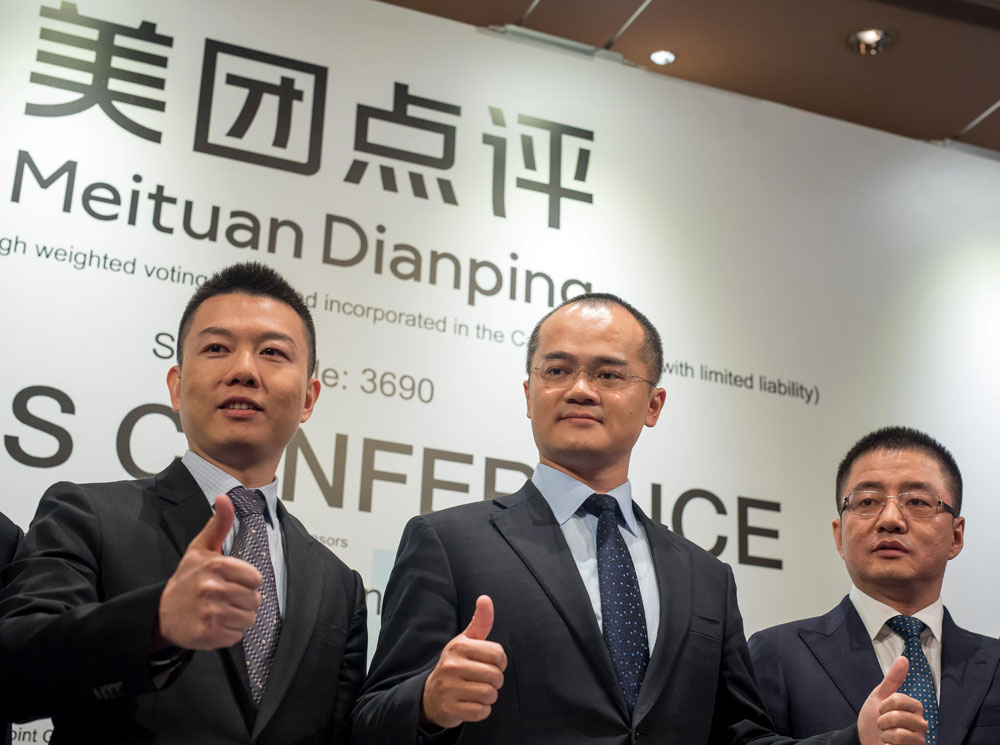 Chen Shaohui, chief financial officer and senior vice president of Meituan Dianping, left, Wang Xing, co-founder and chief executive officer of Meituan Dianping, and Wang Huiwen, senior vice president of Meituan Dianping. (Paul Yeung/Bloomberg)