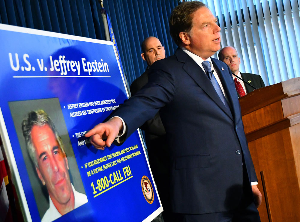 Geoffrey Berman, U.S. attorney for the Southern District of New York, speaks while standing next to a poster displaying the image of fund manager Jeffrey Epstein. (Louis Lanzano/Bloomberg)